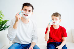 Father and son shaving. Father teaching his son to shave and having fun together Stock Image