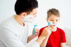 Father and son shaving. Father teaching his son to shave and having fun together Stock Photos
