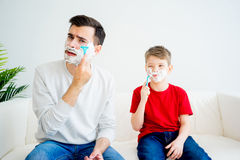 Father and son shaving. Father teaching his son to shave and having fun together Stock Photo