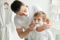 Father and son shaving together. In bathroom stock photography