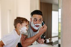 Father and son shaving together in bathroom. Father and son shaving together at home bathroom. Young men and little boy with shaving foam on their faces are Stock Photos