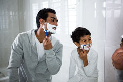 Father and son shaving together. In the bathroom at home Royalty Free Stock Photos
