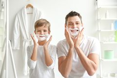 Father and son shaving together. In bathroom Stock Photos