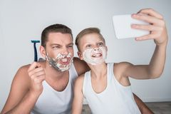 Father and son shaving together. Happy father and son taking selfie while shaving together Royalty Free Stock Photography
