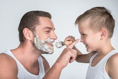 Father and son shaving together. Side view of happy father and son shaving together isolated on grey Royalty Free Stock Image