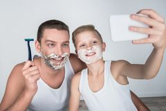 Father and son shaving together. Smiling father and son taking selfie with smartphone while shaving together Royalty Free Stock Images