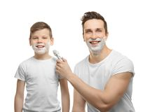 Father and son shaving. On white background Royalty Free Stock Photos