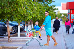 Father and son after shopping in supermarket. Father and son with trolley of food after shopping in supermarket Royalty Free Stock Image