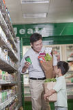 Father and son shopping together in supermarket, holding bags and smiling Stock Photography