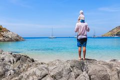 Father and son on the shore of the azure sea watching for drifting yachts. Lifestyle, vacation, happiness, joy concept. Leisure activities Stock Images