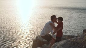 Father with son on shore of lake. Father and son embrace on the shore of a lake on a rock stock video