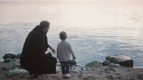 Father and son on the shore, little boy throw stone into the water. Man squatting and show boy how play stone skipping. stock footage