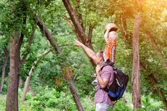Father and son on shoulders in the forest. Summer. Side view.  Royalty Free Stock Photo