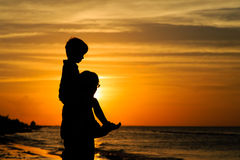 Father and son on shoulders looking at sunset. On the beach Royalty Free Stock Photo