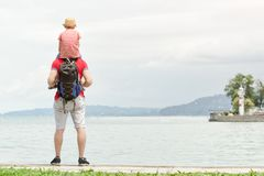 Father and son on shoulders stand on the pier, lighthouse and mountains in the distance. Back view.  Stock Photos