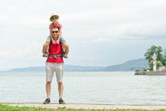 Father and son on shoulders stand on the pier on the sea background, lighthouse and mountains in the distance.  Royalty Free Stock Images