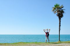 Father with son on shoulders stands back against the backdrop of tall palm, sea and blue sky.  Stock Image