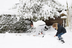 Father and son shoveling snow together in a garden Royalty Free Stock Image