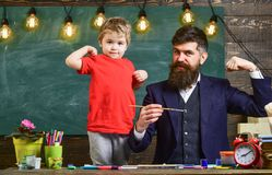 Father and son showing muscles. Dad and kid having fun indoors.  royalty free stock photography