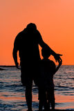 Father and son silhouette. Silhouette of father and son are holding hands at the sea sunset Stock Photos