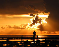 Father and son silhouette sunset. A father with his child silhouetted against a dark orange sunset in Florida Stock Image