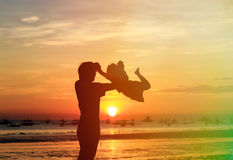 Father and son silhouettes play at the beach Royalty Free Stock Photo