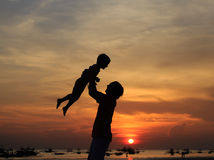 Father and son silhouettes play at sunset Stock Photos