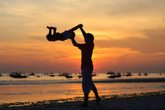 Father and son silhouettes play at sunset Royalty Free Stock Photo