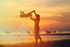 Father and son silhouettes play at sunset Royalty Free Stock Image