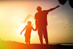 Father and son silhouettes play at sunset Stock Image