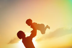 Father and son silhouettes play at sunset Stock Photo