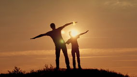 Father and son silhouettes play at sunset beach. Happy family stock video