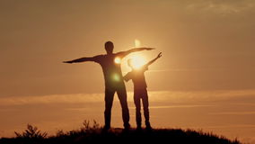 Father and son silhouettes play at sunset beach. Happy family stock video footage