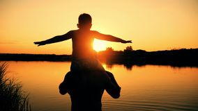 Father and son silhouettes playing on beach boy rising up hands imitating a flight at wonderful sunset through the