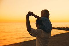 Father and son silhouettes at sunset on a sea beach. Father and son silhouettes at sunset sky. Loving family and summer vacation. Man and kid boy playing Royalty Free Stock Photo