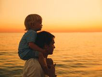Father and son silhouettes at sunset on a sea beach. Father and son silhouettes at sunset sky. Loving family and summer vacation. Man and kid boy playing Stock Photography