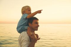 Father and son silhouettes at sunset on a sea beach. Father and son silhouettes at sunset sky. Loving family and summer vacation. Man and kid boy playing Royalty Free Stock Image