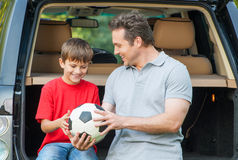 Father and son sit near car with opened boot Stock Photos
