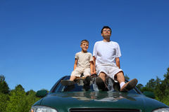 Father with son sit on roof of car in day-time. Father with son sit on roof of car in  day-time and peep into  distance Royalty Free Stock Images