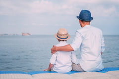 Father and son sit on the sea pier and look on the ship on horiz Stock Photography