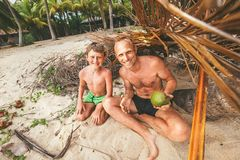 Father and son sit in selfmade hut of branches and play in Robin. Zones Stock Images
