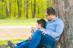 Son and father resting under a tree in the village. Father and son sit under a big tree royalty free stock images