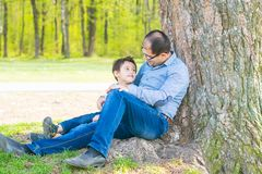 Son and father resting under a tree in the village. Father and son sit under a big tree stock images