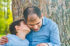 Son and father resting under a tree in the village. Father and son sit under a big tree Stock Photo