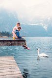 Father with son sit on the wooden pier and look on white swan sw Stock Photography