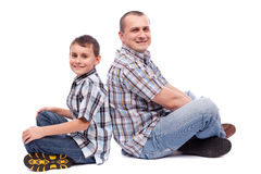 Father and son sitting back to back Stock Photo