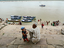 Father and son sitting on the bank of Ganges river in Varanasi, India Stock Photos