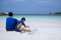 Father and son sitting on beach Stock Photos
