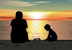 Father and son sitting on the beach, watching sunset Stock Image