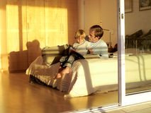 Father and son (5-7) sitting on bed, looking at photo album, view through open sliding doors royalty free stock image